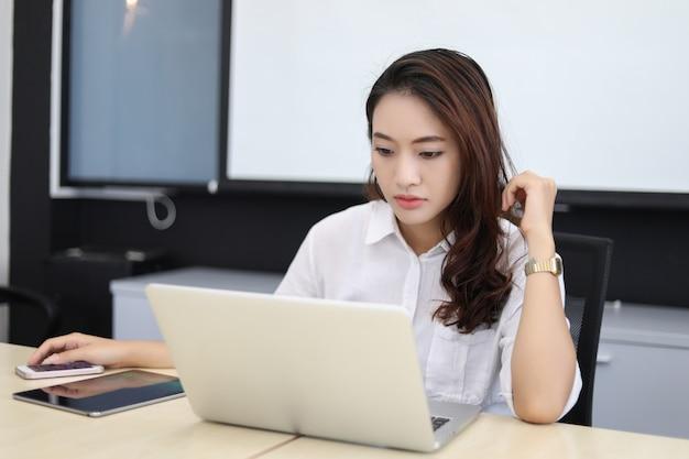 Mulheres de negócios asiáticos usando notebook e grave e dor de cabeça para trabalhar