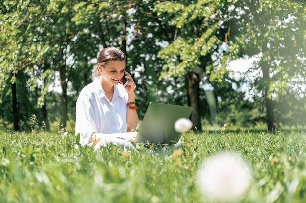 Mulheres de negócios atraentes em camisa branca falando ao telefone usando laptop sentadas na grama no parque