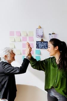 Mulheres de negócios bem-sucedidas cumprimentando-se com um modelo social de