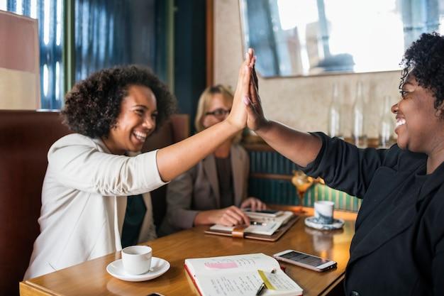Mulheres de negócios bem sucedidos dando um cinco alto