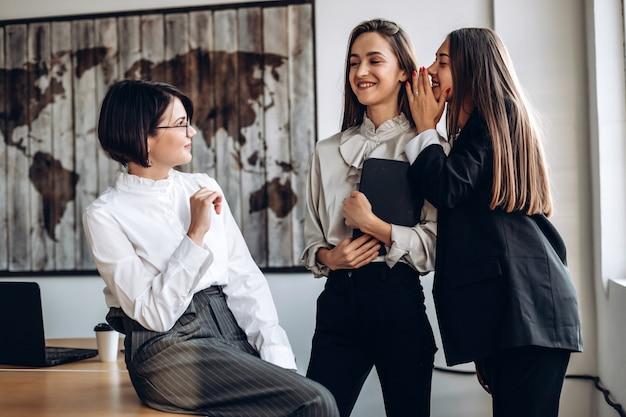Mulheres de negócios bonitas discutem e sussurram entre si