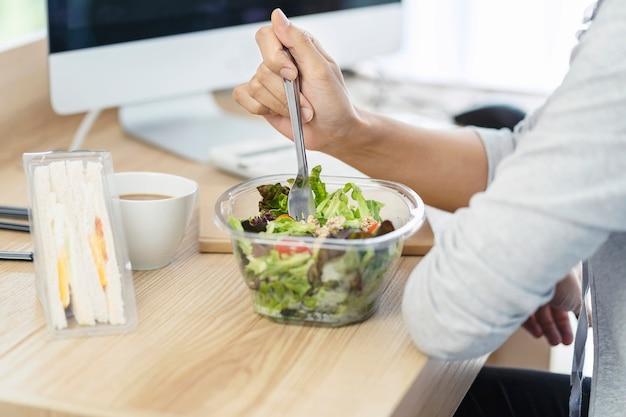 Mulheres de negócios comendo caixa de salada e caixa de sanduíche de ovo. almoçar para trabalhar com parceria no local de trabalho.