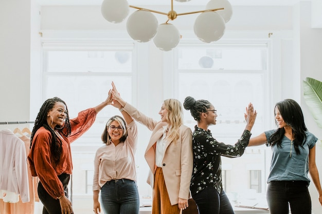 """Mulheres de negócios dando """"high five"""" para a equipe"""