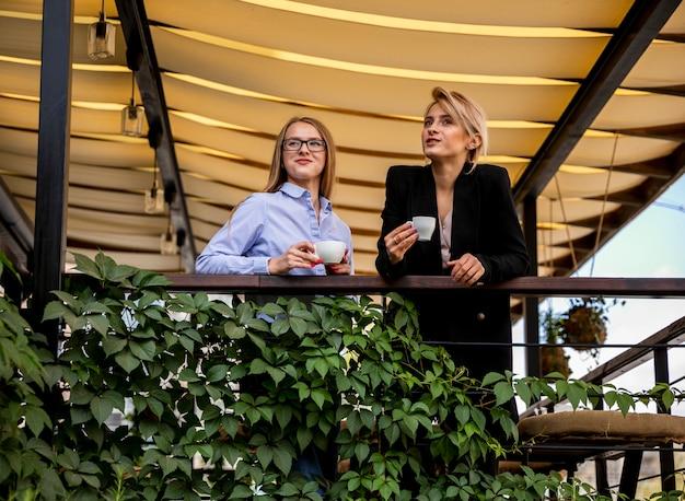 Mulheres de negócios de baixo ângulo na pausa para o café
