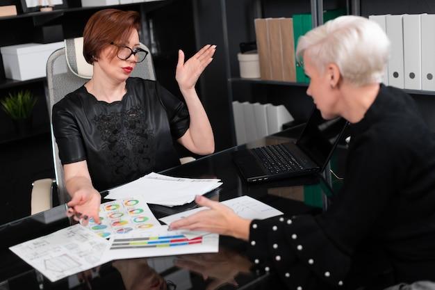Mulheres de negócios discutem diagramas na mesa no escritório