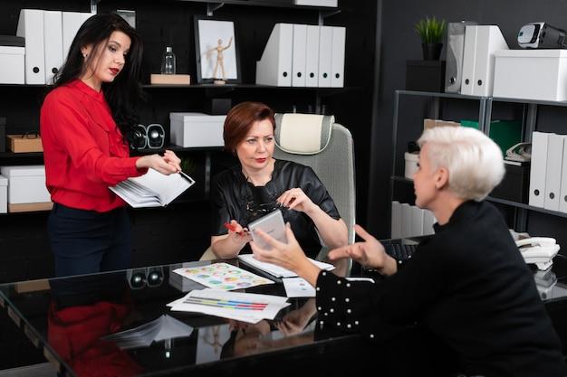 Mulheres de negócios discutem documentos financeiros na mesa no escritório