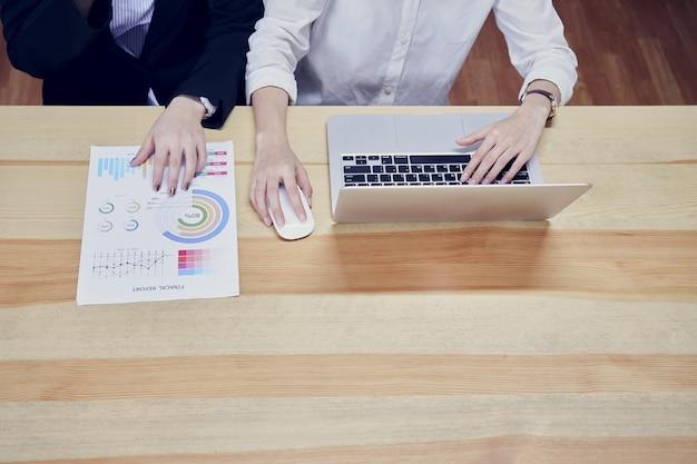 Mulheres de negócios estão usando laptops e documentos financeiros para trabalhar no escritório.