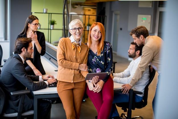 Mulheres de negócios felizes trabalhando juntos on-line em um tablet digital no escritório