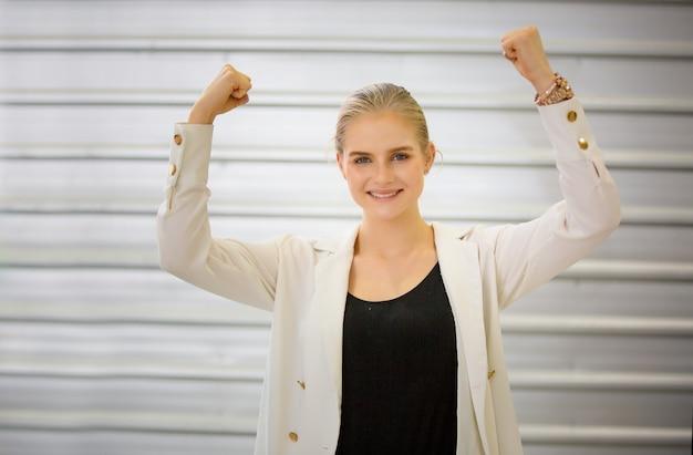 Mulheres de negócios jovem alegre levante a mão em sucesso