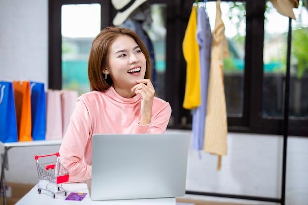 Mulheres de negócios jovens asiáticos trabalhando com laptop em casa