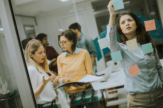 Mulheres de negócios jovens discutindo na frente da parede de vidro usando post-it notes e adesivos
