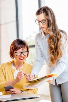 Mulheres de negócios jovens e mais velhas trabalhando juntas em documentos no escritório