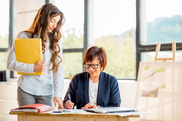Mulheres de negócios jovens e mais velhas trabalhando juntas em documentos no interior de um escritório moderno