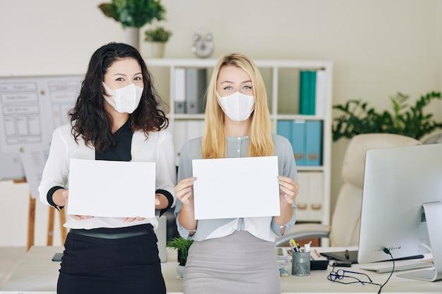 Mulheres de negócios mostrando folhas brancas em branco