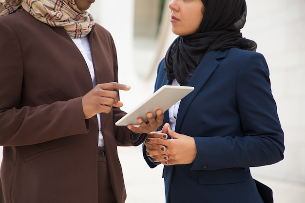 Mulheres de negócios muçulmano usando tablet digital juntos