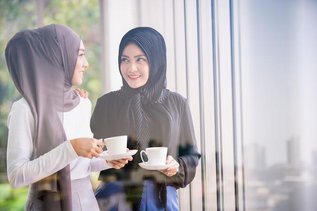 Mulheres de negócios muçulmanos modernos segurando uma xícara de café conversando juntos perto da janela no escritório