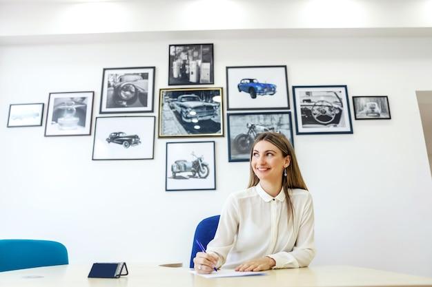 Mulheres de negócios no escritório de inspeção técnica. uma mulher adulta se senta a uma mesa em frente a uma parede branca e segura um lápis na mão enquanto assina papéis. serviço de carro, assinatura de documentação