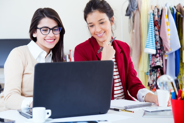 Mulheres de negócios novas que trabalham no portátil