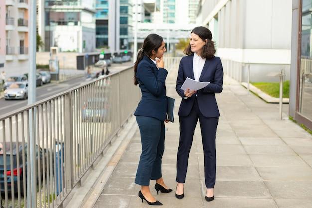 Mulheres de negócios profissionais que discutem papéis