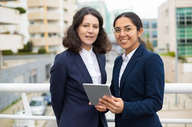 Mulheres de negócios satisfeitas com tabuleta digital