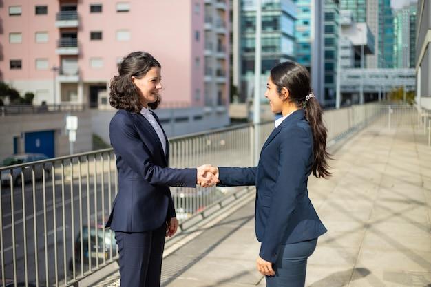 Mulheres de negócios satisfeitas que agitam as mãos