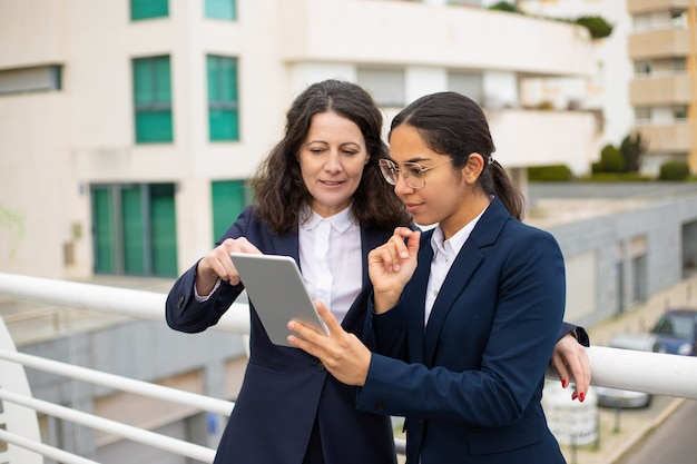 Mulheres de negócios satisfeitas usando o tablet pc