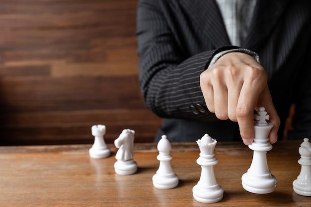 Mulheres de negócios segurando o rei xadrez a bordo desafiam o planejamento da estratégia de negócios para o sucesso