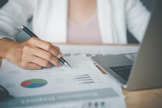 Mulheres de negócios, sentadas em um laptop e verificando documentos gráficos de negócios, trabalhando em transações financeiras, contabilidade