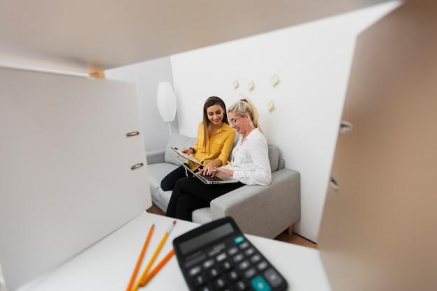 Mulheres de negócios, sentado no sofá e trabalhando no laptop