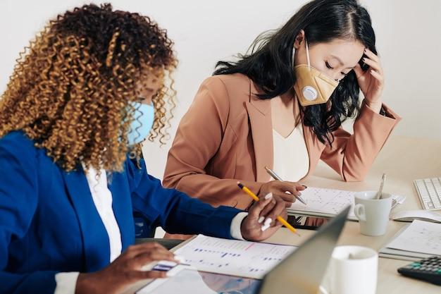 Mulheres de negócios sérias e concentradas usando máscaras protetoras, analisando relatórios financeiros ao trabalhar com vários gráficos na mesa do escritório