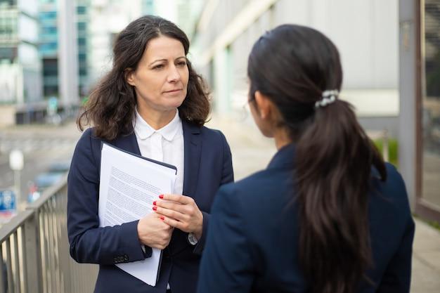 Mulheres de negócios sérios falando na rua