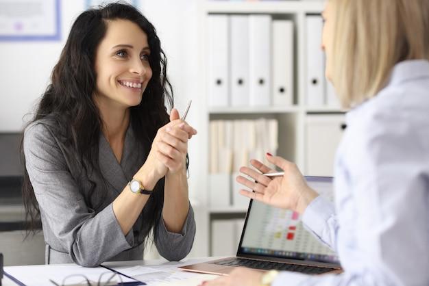 Mulheres de negócios, sorrindo e conversando à mesa no emprego de escritório do conceito de pessoal