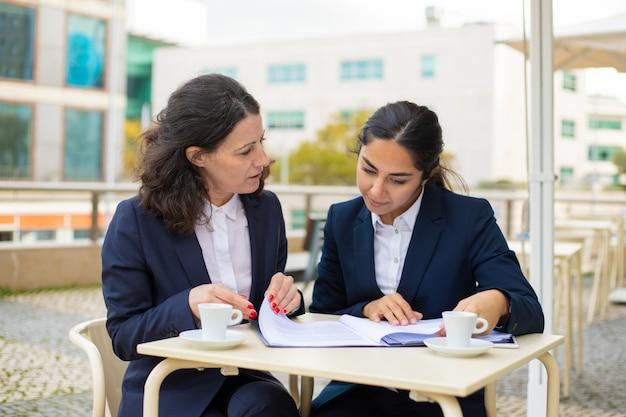 Mulheres de negócios trabalhando com papéis no café ao ar livre