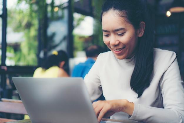 Mulheres de negócios, trabalhando on-line em um café.