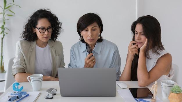 Mulheres de negócios vista frontal trabalhando em um laptop