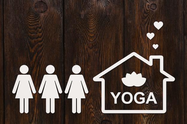 Mulheres de papel e casa com texto ioga dentro de madeira