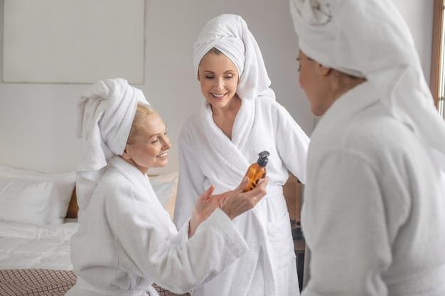 Mulheres de roupão discutindo novo produto cosmético