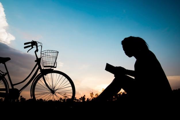 Mulheres de silhueta, lendo o livro com bicicleta