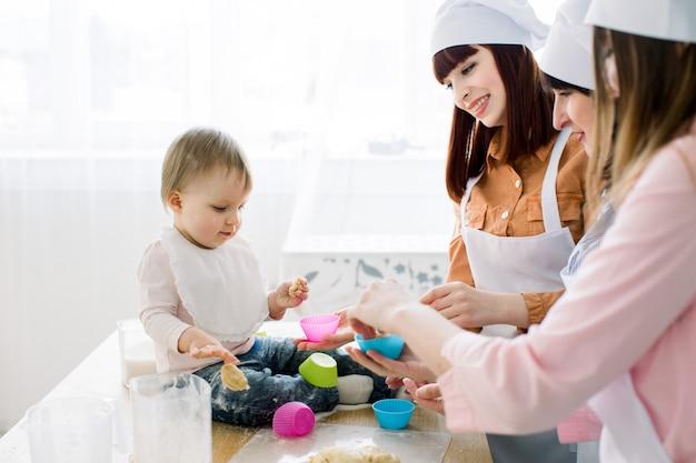 Mulheres de sorriso felizes que cozem junto com a cozinha pequena do bebê em casa, dia de mães, conceito de família. as mulheres estão colocando massa em copos de silicone coloridos para bolos