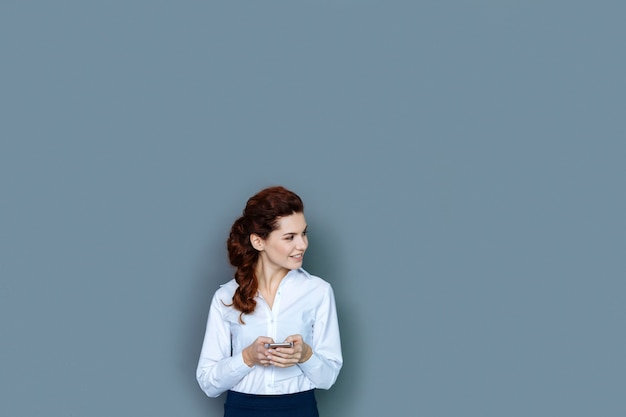 Mulheres de sucesso. mulher de negócios atraente, positiva e encantada, sorrindo e olhando para o lado enquanto fica feliz com seu sucesso profissional