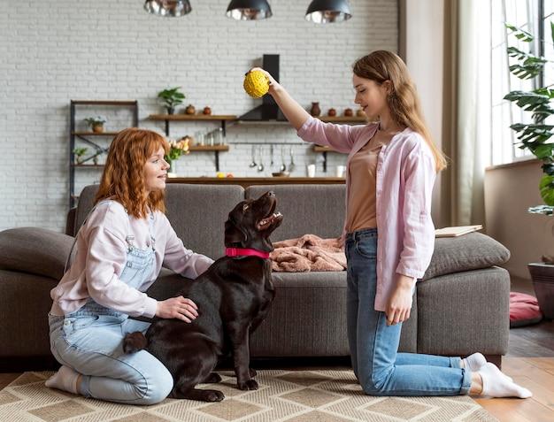 Mulheres de tiro completo e cachorro com bola