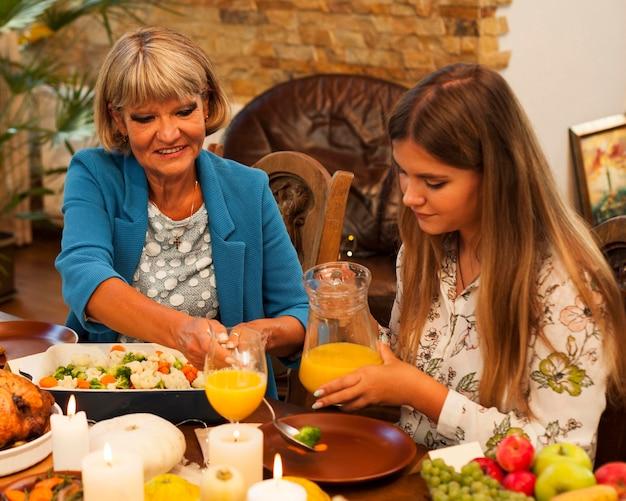 Mulheres de tiro médio à mesa de jantar
