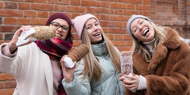 Mulheres de tiro médio com bolos de chaminé
