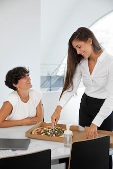 Mulheres de tiro médio com pizza