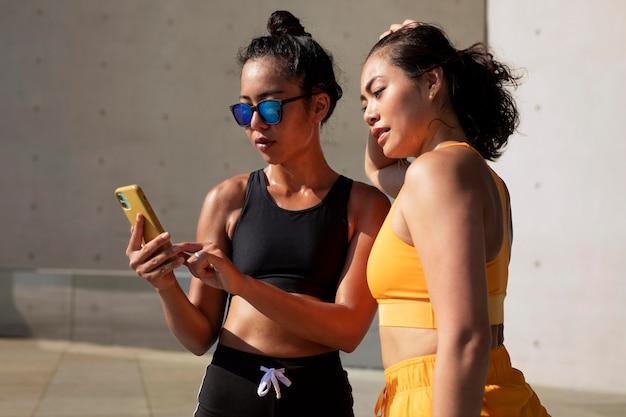 Mulheres de tiro médio com smartphone