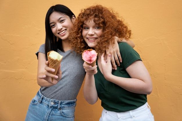 Mulheres de tiro médio com sorvete
