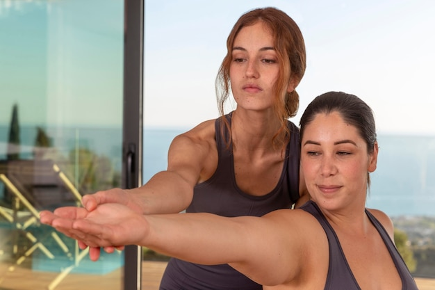 Mulheres de tiro médio fazendo ioga juntas
