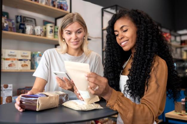 Mulheres de tiro médio lendo rótulos