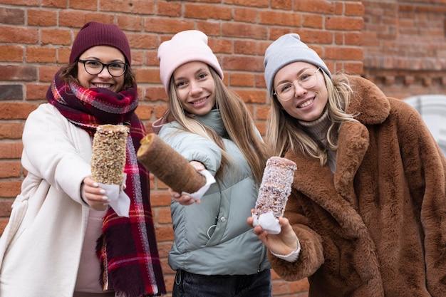 Mulheres de tiro médio posando com bolos de chaminé