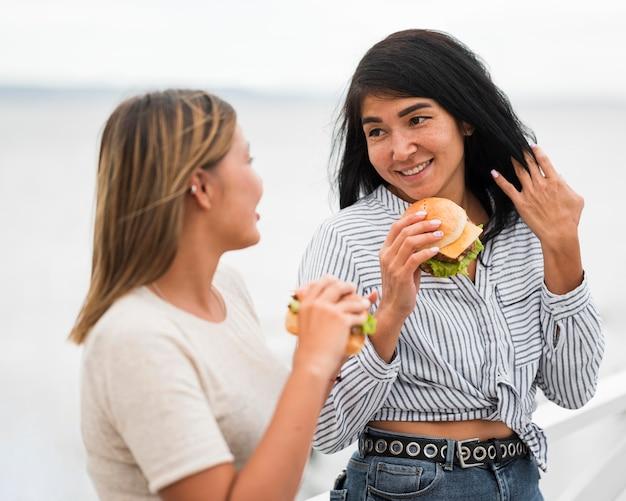 Mulheres de tiro médio segurando hambúrgueres